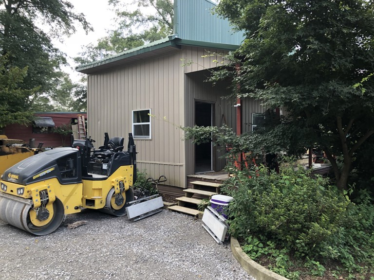 A little storage house on the property is converted to a cabin for guests while a driveway is prepared