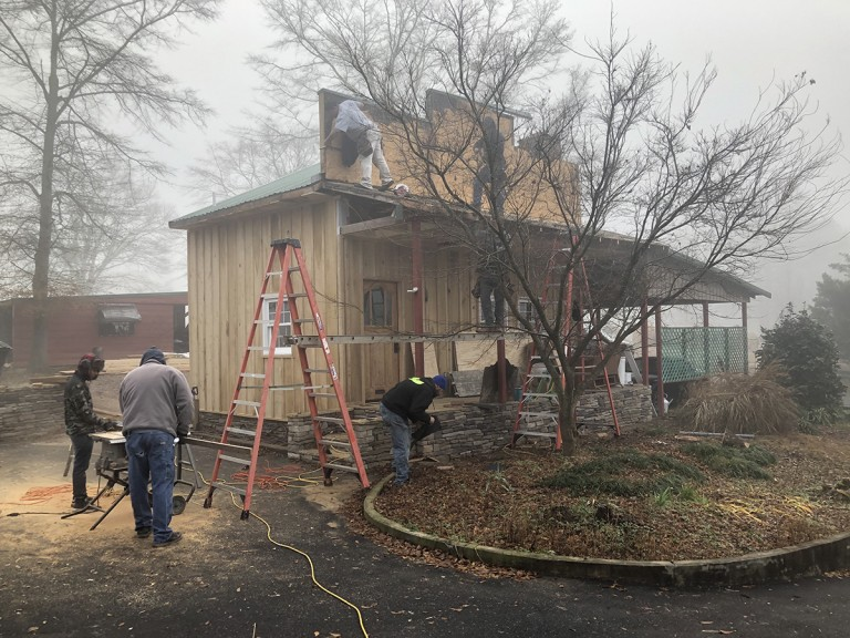 At this stage, stone and concrete replaces the old railroad ties the previous builder used for a foundation, plastic siding has been replaced by locally milled poplar, and the roof is well underway